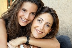 two girls hugging and smiling, one has braces